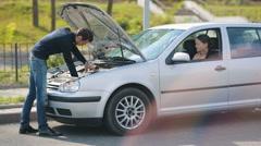 Woman help to man repair broken car Stock Footage