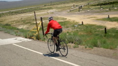 A man road biking on a scenic road, slow motion. Stock Footage