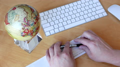 Top shot of bsiness man writing a cheque with globe spinning inside office Stock Footage
