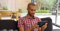 4k, Young man playing an online game on his digital touchscreen tablet. Stock Footage