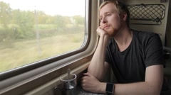 Man Looking Out the Window While Sitting in the Train and Falls Asleep Stock Footage