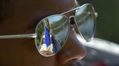 Extreme close-up of man wearing sunglasses resting in a hammock near a mountain Stock Footage