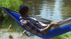 A man resting in a hammock near a mountain lake, slow motion. Stock Footage