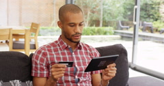 4k, Happy young African American man shopping with credit card & digital tablet Stock Footage