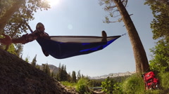 A man resting in a hammock with his dog near a mountain lake. Stock Footage
