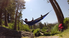 A man resting in a hammock and using a tablet mobile device near a mountain lake Stock Footage