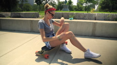 A young woman stretching next to her longboard skateboard. Stock Footage