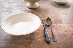 Antique plate and tableware on aged wooden table Stock Photos