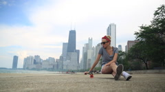 A young woman goes longboard skateboarding with the Chicago, Illinois skyline in Stock Footage