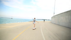 Tracking shot of a young woman going longboard skateboarding. Stock Footage