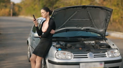 Woman with broken car calling by the phone Stock Footage