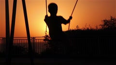 Silhouette of a boy on a swing in the sunset. Stock Footage