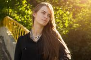 Young woman on the background of trees and sunlight Stock Photos