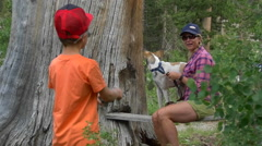 A woman and her dog pose for a picture to be taken by her boy, slow motion. Stock Footage