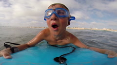 A boy wearing goggles and sinking under waves while body boarding at the beach, Stock Footage
