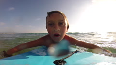 A boy body boarding in the waves, slow motion. Stock Footage