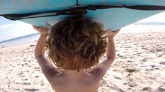 A boy holding his board to go body boarding at the beach, slow motion. Stock Footage