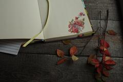 Open Notepad with autumn culinary sticker rests on a wooden background Stock Photos