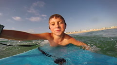 A boy body boarding and sinking under waves at the beach. Stock Footage