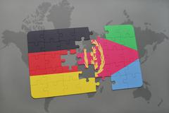 Puzzle with the national flag of germany and eritrea on a world map backgroun Stock Photos