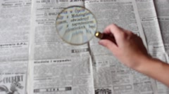 Reading the newspaper through a magnifying glass Stock Footage