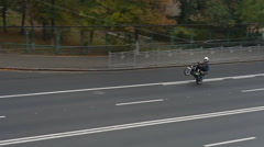 Biker rides on rear wheel of scooter on the street Stock Footage