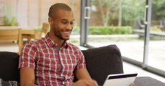 4k, Young African American man having a video chat on his laptop from home. Stock Footage