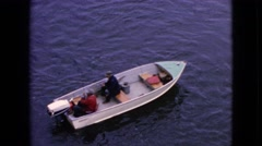 1964: two people driving a small boat in still water seems to be fishing  Stock Footage