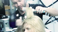 Stylist Making Hairdo for Beautiful Blonde Stock Footage