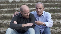 Elderly father consoles his son on the steps in a park Stock Footage