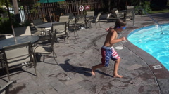 A boy doing a cannonball and jumping into a pool at a hotel resort, super slow m Stock Footage