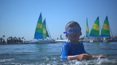 A boy playing in the water of Mission Bay, San Diego, super slow motion. Stock Footage