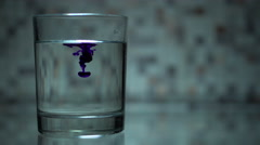 Blue colorant is dissolved in glass of water Stock Footage