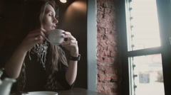 Woman using her smartwatch touchscreen device drinking coffee looking out the Stock Footage