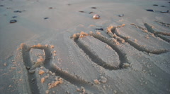 ROCKLANDS letters written in the sand at the beach. Stock Footage