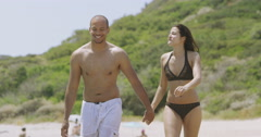 4K Attractive couple holding hands as they walk along a beach Stock Footage