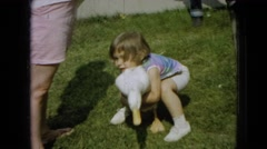 1965: duck, girl, lawn grass sidewalk family white waddle pick up carry smile Stock Footage