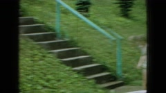 1965: cute little girls playing park sprinkling water sliding stairs trees Stock Footage