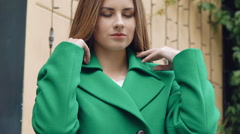 Stylish girl corrects green coat and smiling Stock Footage