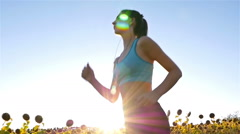 Woman girl with headphones running jogging in sunflower field, slow motion Stock Footage