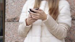 Smart girl taking selfie in fur jacket near the building Stock Footage