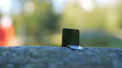 Smart Watch is on a large stone in the street. Moving the camera Stock Footage
