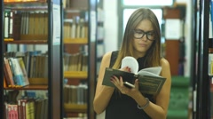 A female college student studies in the library Stock Footage