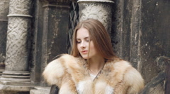 Pretty girl posing in furry jacket on the street and smiling at camera Stock Footage
