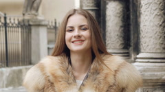 Cute girl posing in furry jacket on the street and smiling Stock Footage