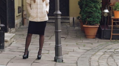 Fashionable girl posing in furry jacket on the street Stock Footage