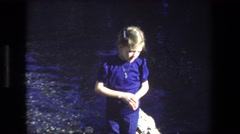 1972: girl standing by lake near monument ISRAEL Stock Footage