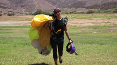 A woman skydiver walks holding her parachute and smiling. Stock Footage
