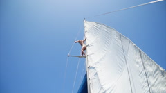 A topless woman jumps off the mast of a sailboat into the ocean. Stock Footage