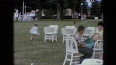 1967: park outing boys girls ladies women chairs tables grass trees lampstands Stock Footage
